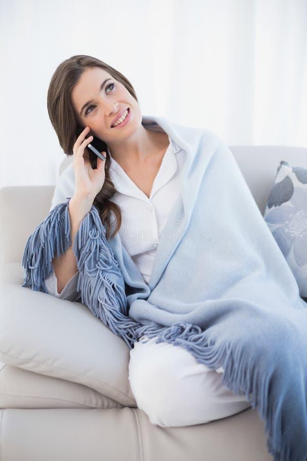 Donna dai capelli marrone abbastanza casuale in pigiami bianchi che fanno una telefonata fotografia stock