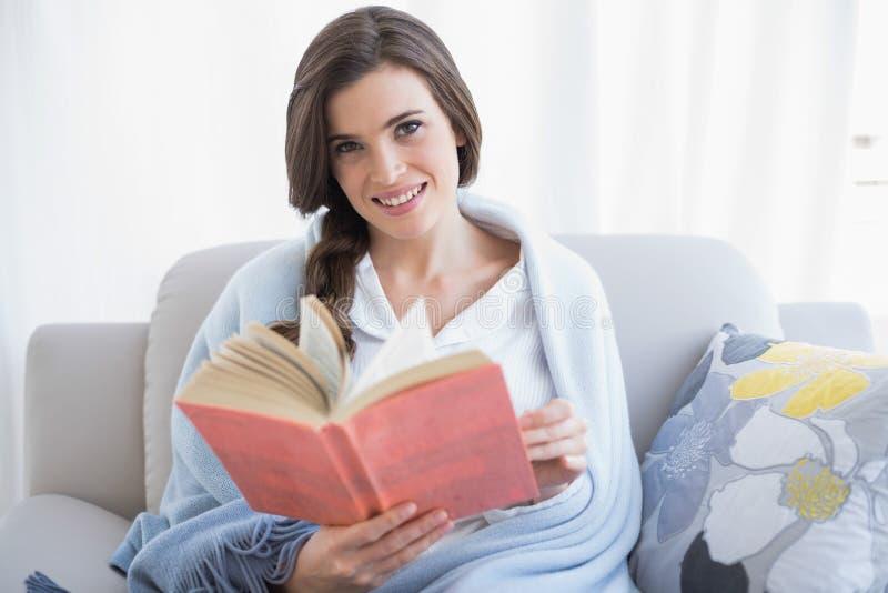 Donna dai capelli marrone abbastanza casuale in pigiami bianchi che legge un libro fotografia stock