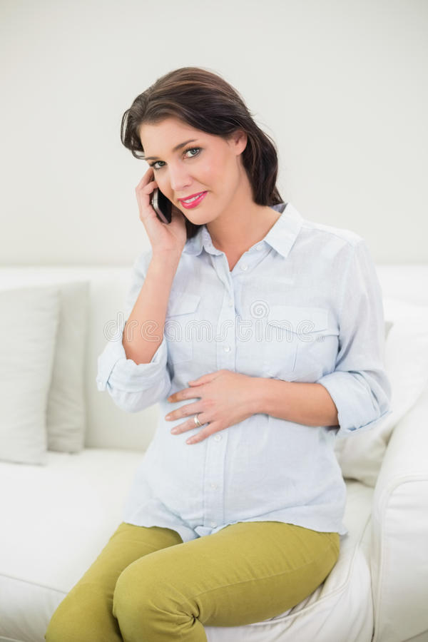 Donna dai capelli marrone incinta contenta che fa una telefonata fotografie stock