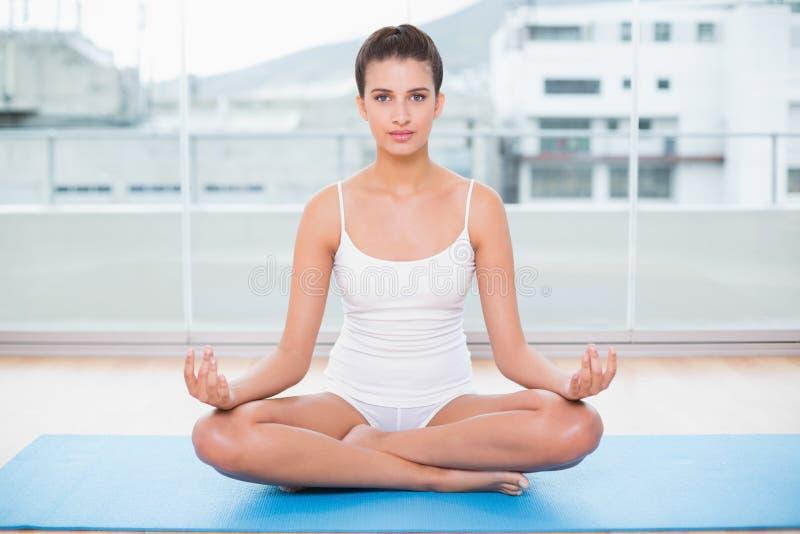 Donna dai capelli marrone naturale calma nell'yoga di pratica degli abiti sportivi bianchi fotografia stock