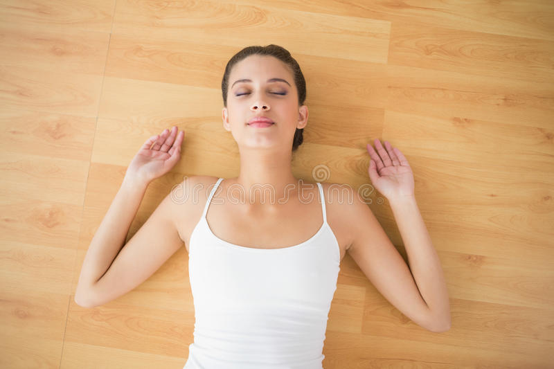 Donna dai capelli marrone naturale contenta in abiti sportivi bianchi che dorme sul pavimento immagine stock libera da diritti