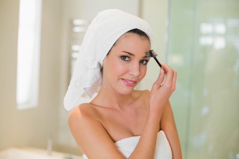 Donna dai capelli marrone naturale contenta che spazzola le sue sopracciglia immagine stock