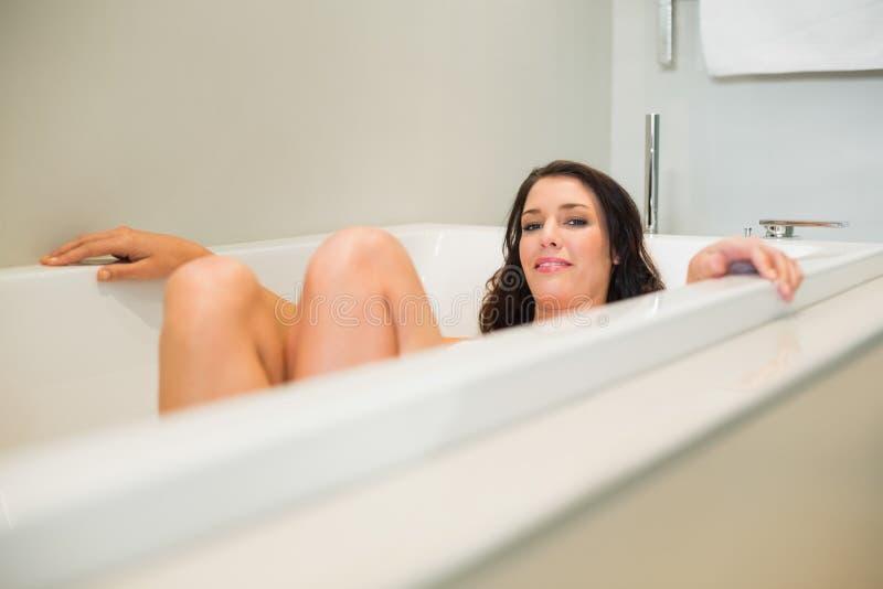 Donna dai capelli marrone naturale sorridente che si rilassa in una vasca immagine stock