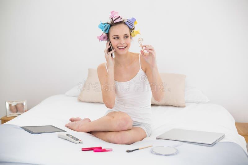 Donna dai capelli marrone naturale sveglia in bigodini che fanno una telefonata e che tengono un bigodino del ciglio immagine stock