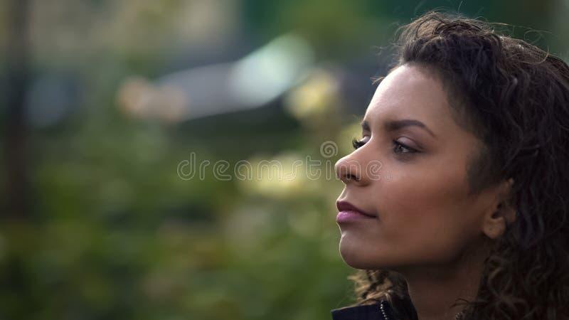 Donna dai capelli riccia biraziale vaga che guarda lontano, pensando alla vita, primo piano fotografia stock