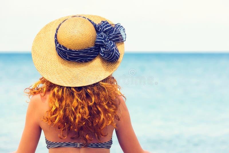 Donna dai capelli riccia che esamina il mare fotografia stock