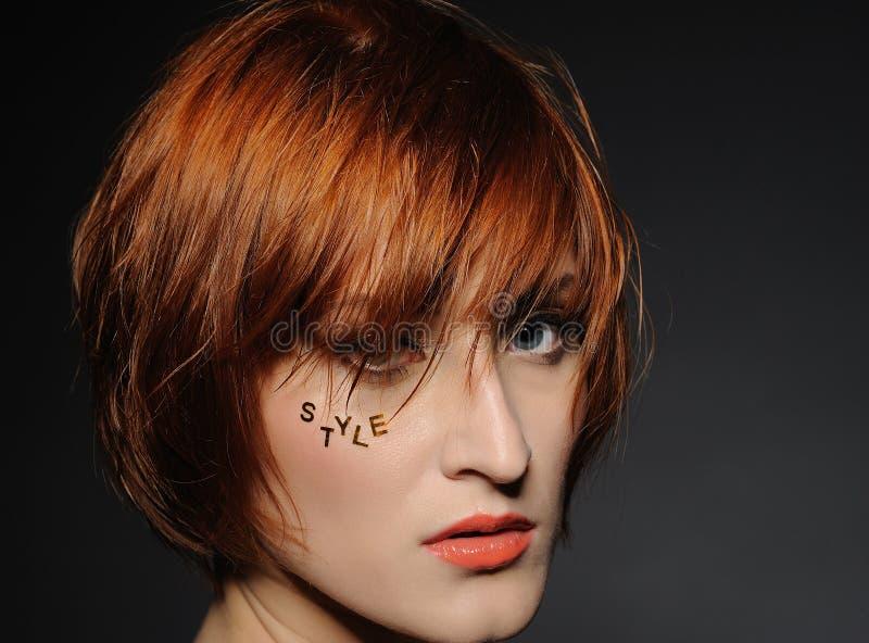 Donna dai capelli rossa con l'acconciatura di modo fotografie stock