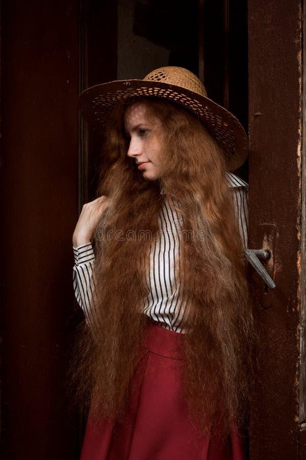 Donna dai capelli rossi abbastanza giovane con le lentiggini nella posa del cappello di paglia fotografia stock