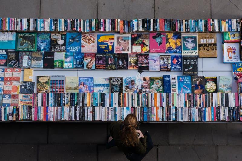 Donna dai capelli rossi che passa in rassegna i libri di seconda mano al bookmarket fotografia stock
