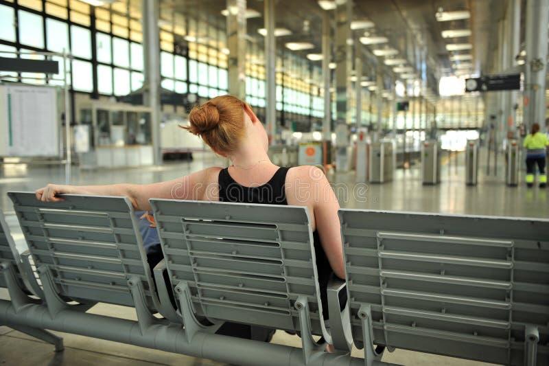 Donna dai capelli rossi che si siede nell'attesa della stazione fotografia stock