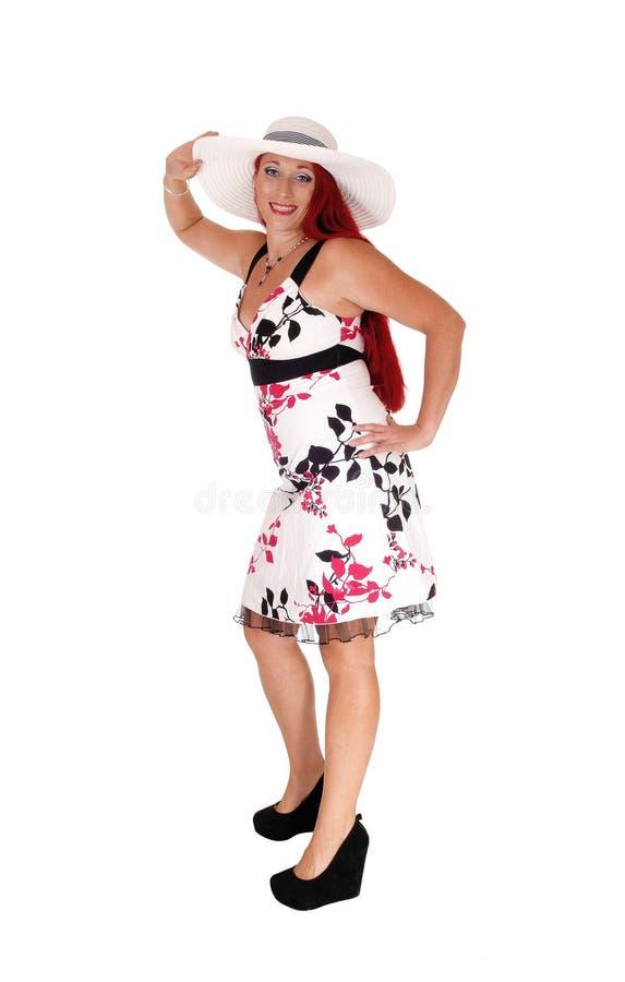 Donna dai capelli rossi che sta con il cappello immagini stock libere da diritti