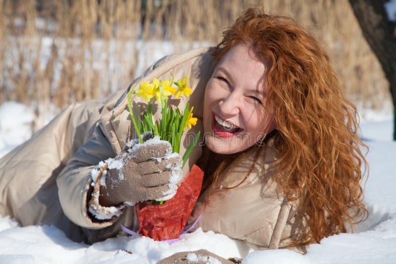 Donna dai capelli rossi ottimista che tiene i narcissuses in mani mentre trovandosi nella neve immagini stock libere da diritti