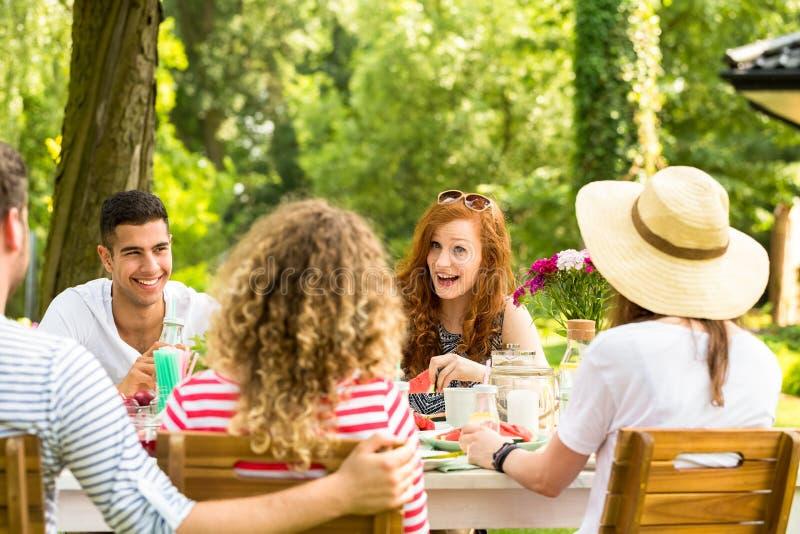 Donna dai capelli rossi sorridente divertendosi durante il ricevimento all'aperto con mul fotografie stock