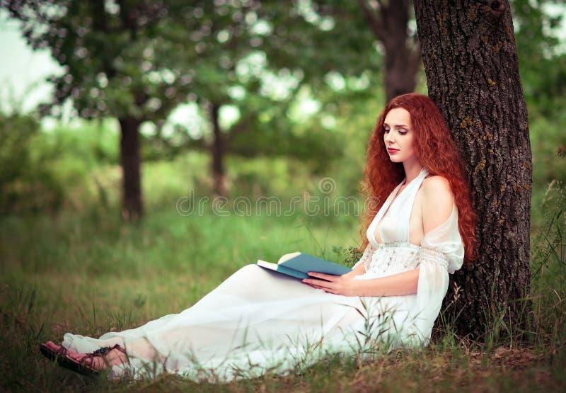 Donna dai capelli rossi sveglia che si siede sotto l'albero e che legge un libro fotografie stock libere da diritti