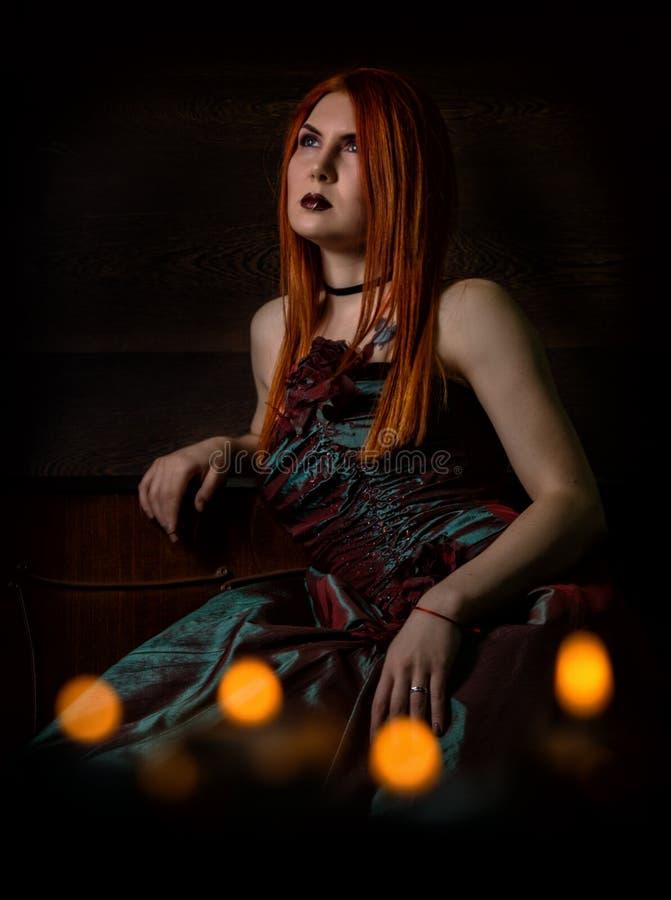 Donna dai capelli rossi in un retro vestito con le candele su fondo nero fotografia stock