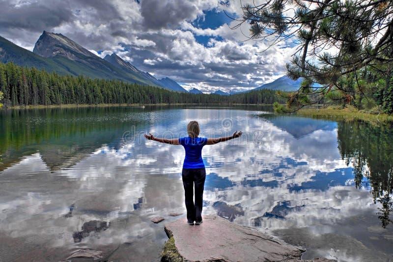 Donna dal lago alpino con la riflessione delle nuvole e delle montagne fotografia stock libera da diritti