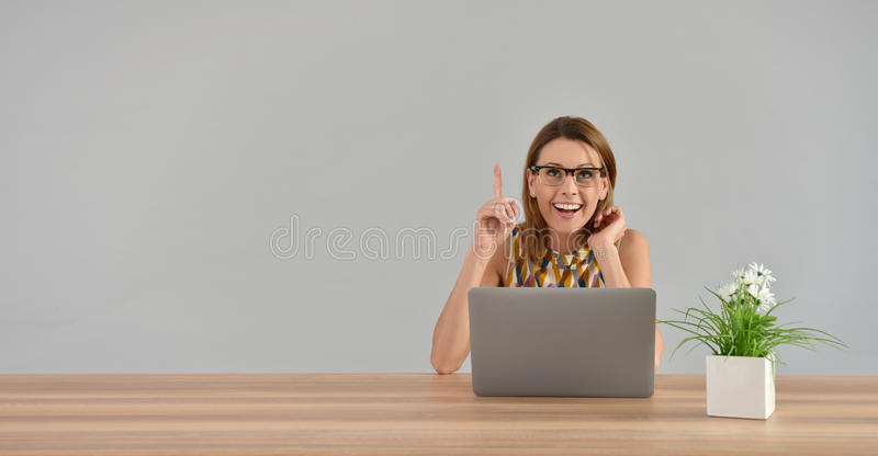 Donna davanti al computer portatile che ottiene una buona idea fotografie stock