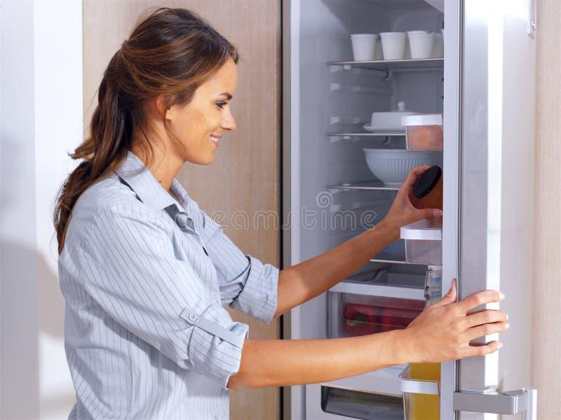 Donna davanti al frigorifero fotografia stock libera da diritti