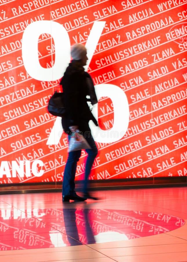 Donna davanti al segno di vendite fotografie stock