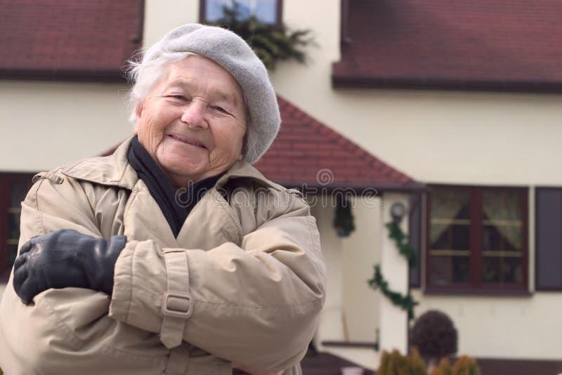 Donna davanti alla casa. immagine stock