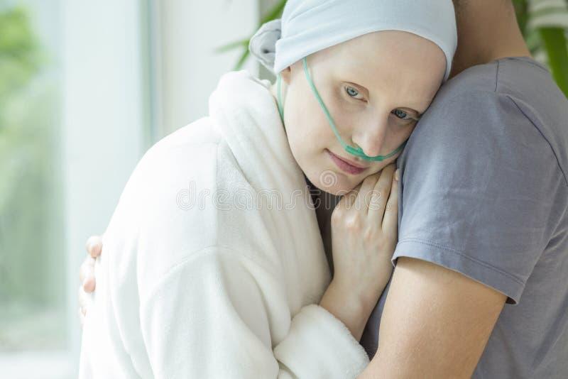 Donna debole con cancro che abbraccia il suo marito durante la chemioterapia fotografie stock
