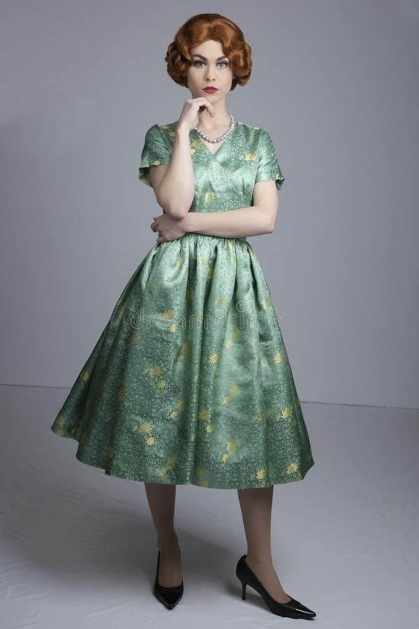 donna degli anni 50 in vestito verde dal raso fotografia stock libera da diritti