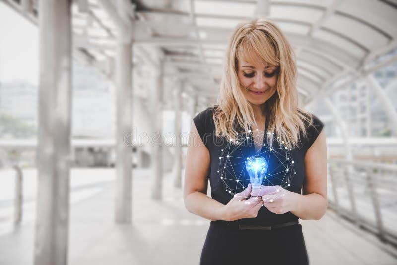 Donna dei capelli biondi che tiene e che esamina lampadina blu con la linea effetto di lustro e luminosa dell'illustrazione del p immagine stock libera da diritti