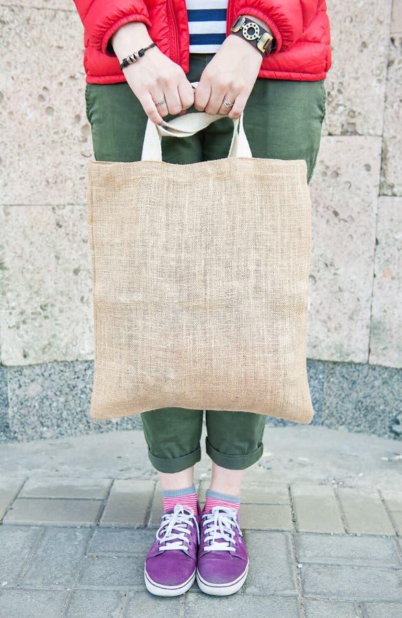 Donna dei pantaloni a vita bassa che giudica la borsa vuota della tela all'aperto Derisione del modello su immagine stock
