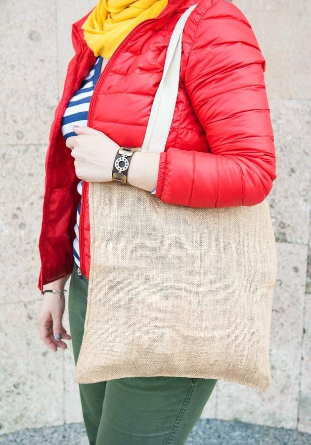 Donna dei pantaloni a vita bassa che giudica la borsa vuota della tela all'aperto Derisione del modello su fotografia stock libera da diritti