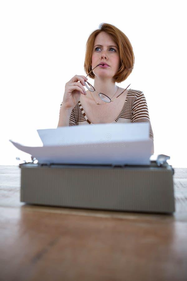 donna dei pantaloni a vita bassa che pensa davanti alla sua macchina da scrivere fotografia stock libera da diritti