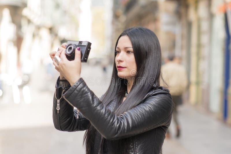 Donna dei pantaloni a vita bassa che prende le immagini con la macchina fotografica di classica fotografia stock