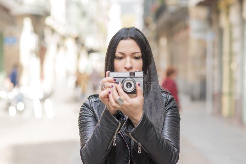 Donna dei pantaloni a vita bassa che prende le immagini con la macchina fotografica di classica fotografie stock