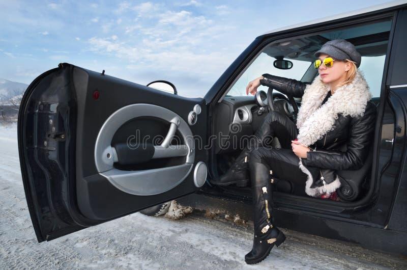 Donna dei pantaloni a vita bassa che si siede in una piccola automobile immagini stock libere da diritti