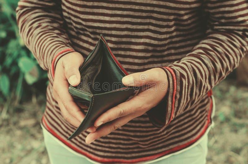 donna dei pantaloni a vita bassa che tiene un portafoglio vuoto fotografia stock libera da diritti