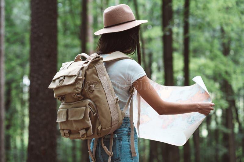 Donna dei pantaloni a vita bassa del viaggiatore in foresta con lo zaino che cerca direzione sulla mappa fotografia stock