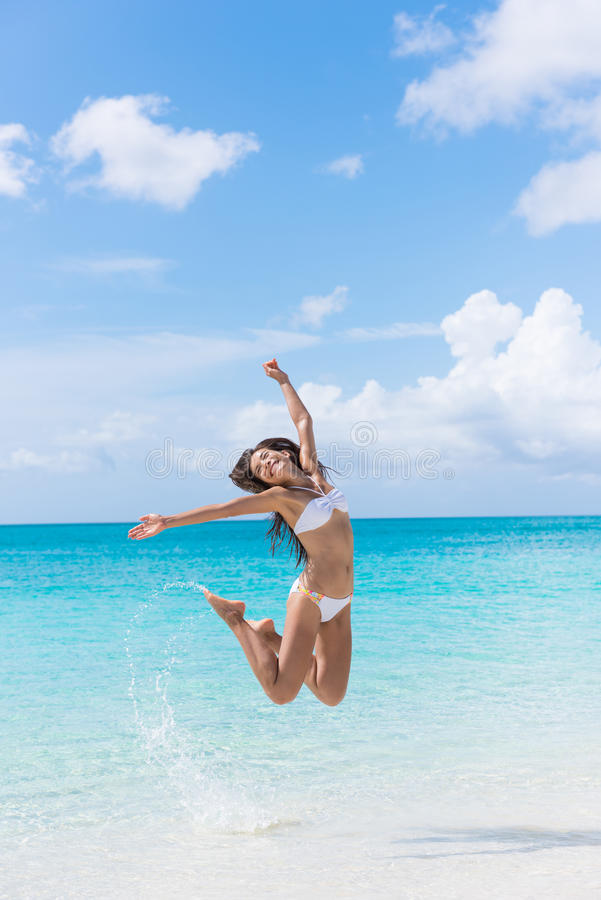 Donna del bikini di divertimento che salta sulla spiaggia che spruzza acqua fotografie stock libere da diritti