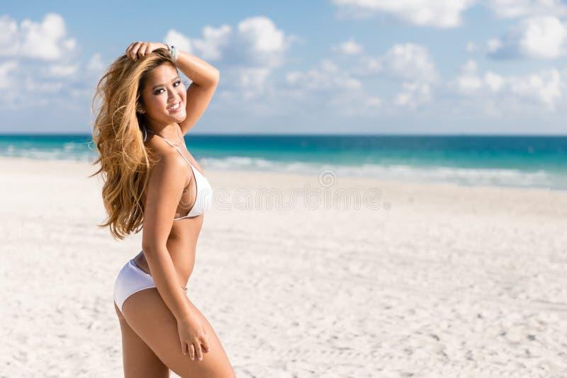 Donna del bikini sulla spiaggia tropicale con acqua dell'oceano del turchese durante fotografia stock libera da diritti