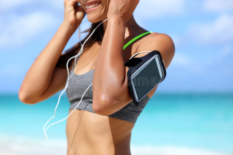 Donna del bracciale del telefono di forma fisica che mette le cuffie fotografia stock libera da diritti