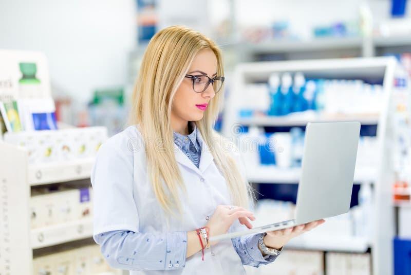 Donna del chimico del farmacista che sta nella farmacia della farmacia e che per mezzo del computer portatile per i media del soc fotografia stock