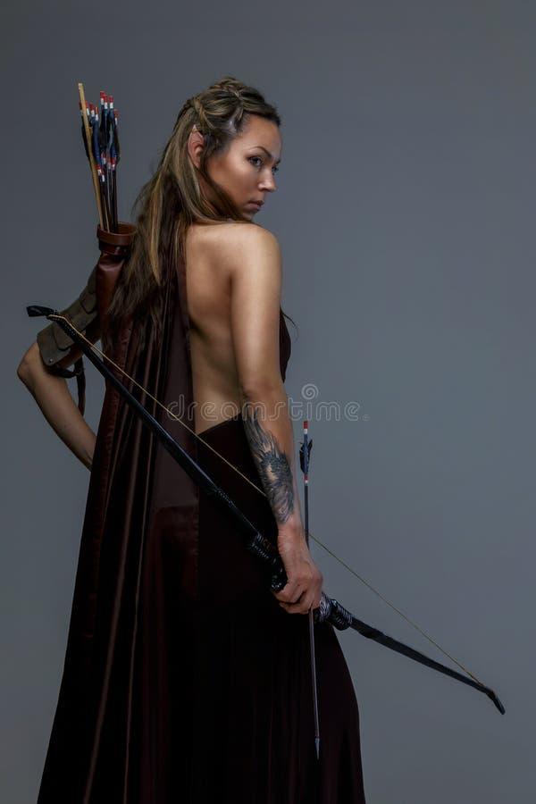 Donna del combattente nell'arco del witj dell'armatura fotografie stock