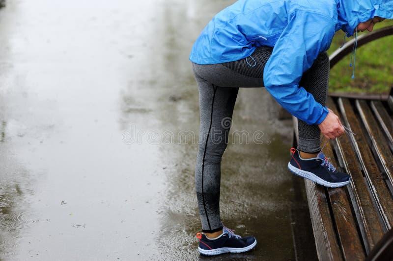 Donna del corridore che lega i pizzi prima della formazione nella pioggia Maratona fotografia stock libera da diritti