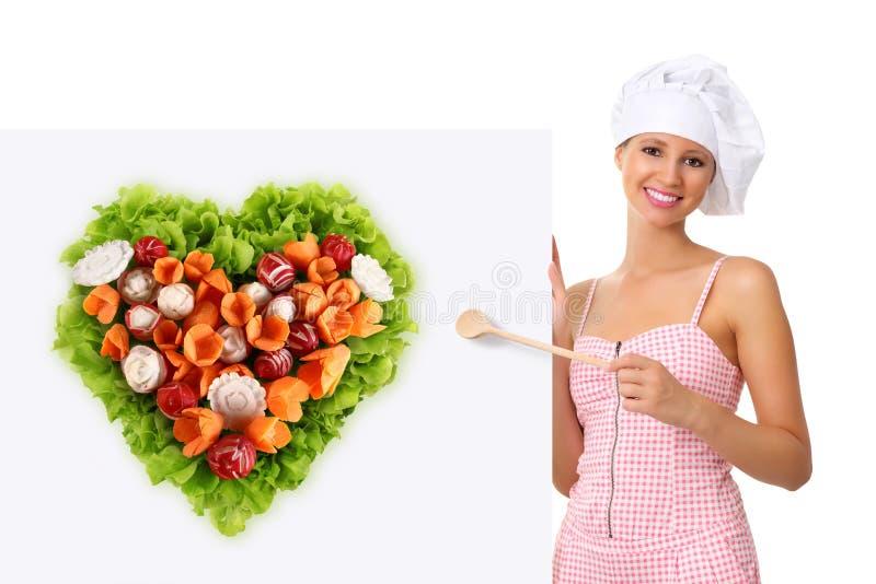 Donna del cuoco unico che indica con un cucchiaio di legno sul tabellone per le affissioni bianco fotografia stock