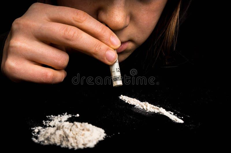 Donna del drogato che sniffa la polvere della cocaina con la banconota rotolata immagine stock libera da diritti