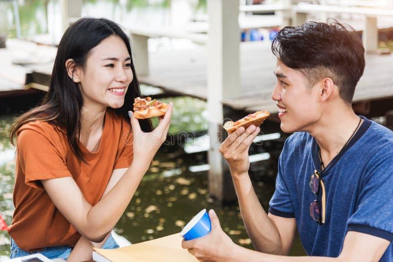 Donna del gruppo di studenti e pizza mangiatrice di uomini insieme immagini stock