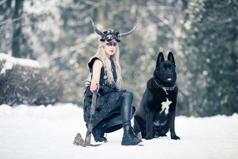 Donna del guerriero nell'immagine di vichingo con l'ascia ed il casco cornuto accanto al cane nella foresta di inverno fotografie stock
