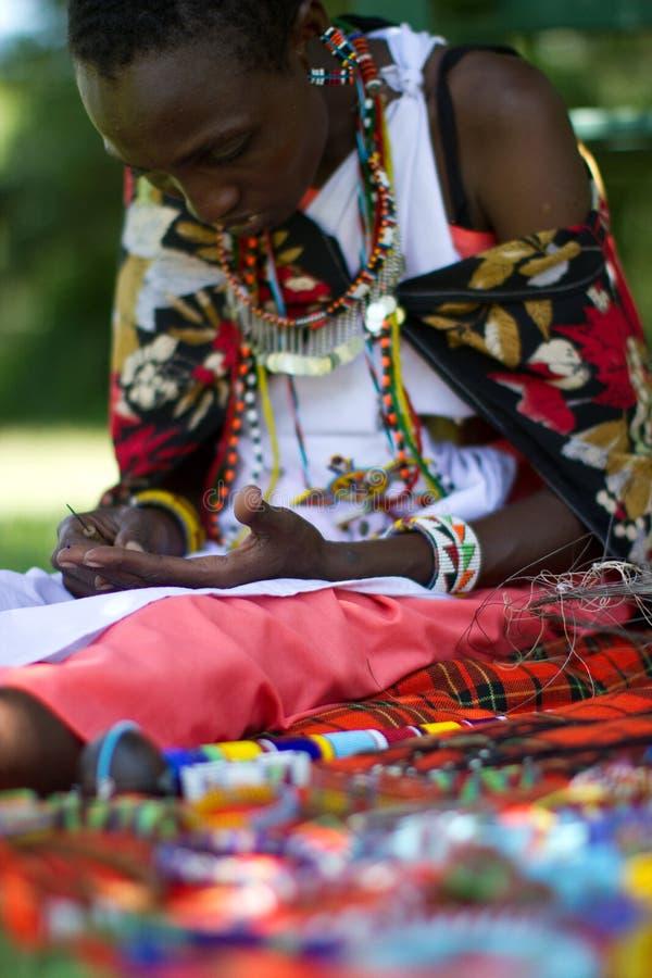 Donna del Masai che seleziona i branelli immagini stock