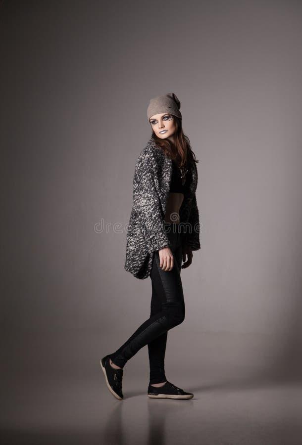 Donna del modello di moda che posa cappello d'uso e cappotto nero fotografia stock libera da diritti