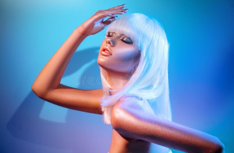 Donna del modello di moda nelle scintille luminose variopinte e nelle luci al neon che posano nello studio fotografia stock libera da diritti