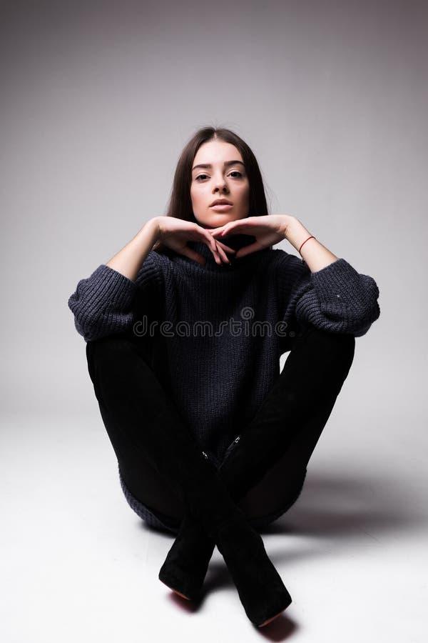 Donna del modello di moda in vestiti moderni che si siedono sul pavimento isolato su fondo bianco fotografie stock libere da diritti