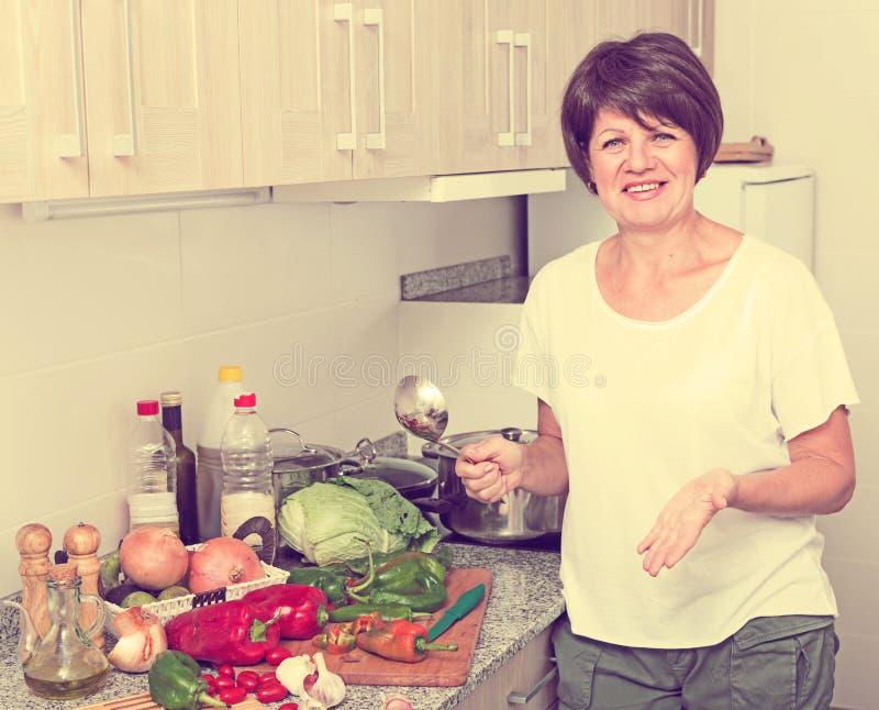 Donna del pensionato che cucina minestra fotografie stock